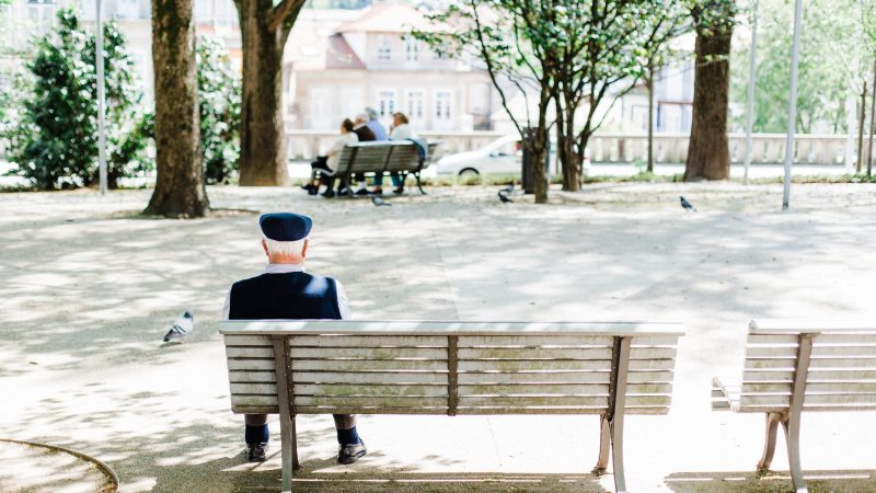 Elderly man on bench by himself outdoors